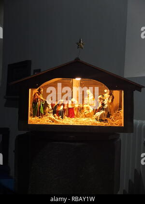 Illuminated crib nativity scene in a church for Christmas (St Edmunds Church, Castleton, Derbyshire, UK) - Stock Photo