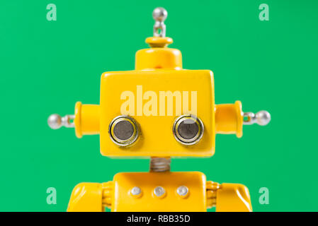 Portrait of a Cute, yellow, handmade robot on a green background. - Stock Photo