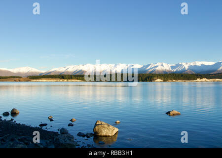 Lake Tepako Sunrise in New Zealand. a clear sky reflect in the lake with snow topped mountains and green Forna showing the changing seasons - Stock Photo