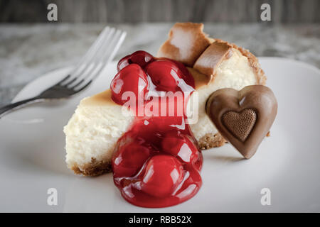 New York style cheesecake with cherries and a chocolate heart on white plate.  Fork in the background. - Stock Photo