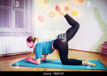 Portrait of gorgeous young woman practicing yoga indoor. Beautiful girl practice yoga in peaceful ambient. Calmness and relax, female happiness. - Stock Photo