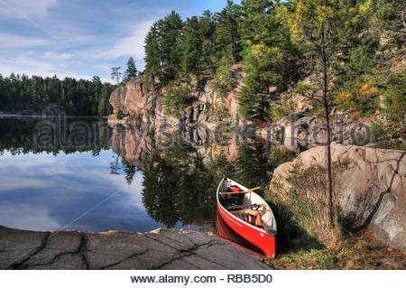 Solitary red canoe on shore of  wilderness setting at rock shoreline of George Lake Killarney Park - Stock Photo