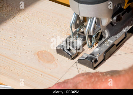 young man carpenter builder working with electric jigsaw and wood.hobby concept.DIY acronym cut out in OSB panel with electric jigsaw.Woodworker cutting a piece of wood - Stock Photo