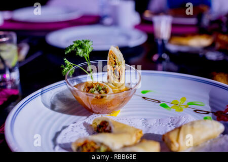 Fried spring rolls with red and white sauces, served in white plate with fresh green salad over gray background. Asian food. Crispy golden fried vegetable spring rolls with fresh ingredients an oriental restaurant - Stock Photo