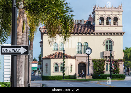 Woman riding bicycle in front of the historic Town Hall in Palm Beach, Florida. (USA) - Stock Photo