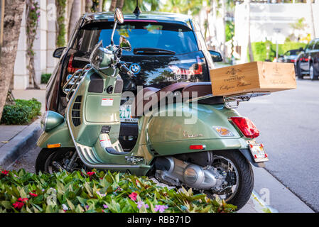 Vespa motor scooter with Tuscan wine crate outside of Saks Fifth Avenue at the Esplanade on Worth Avenue in Palm Beach, Florida. (USA) - Stock Photo