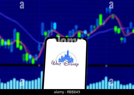 Walt Disney logo is seen on an smartphone over stock chart - Stock Photo