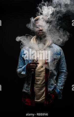 Man smoking or vaping e-cig or electronic cigarette holding a mod with a lot of clouds - Stock Photo