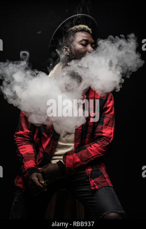 Young african man on a black background holding an electronic cigarette, vaping device, mod, e-cig on black background - Stock Photo