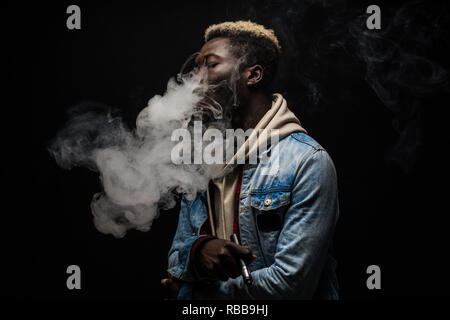 African Man vaping an electronic cigarette isolated on black - Stock Photo