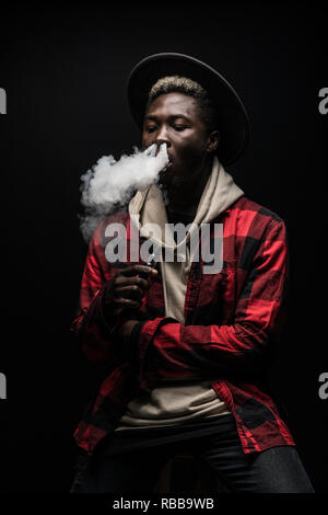 Young thinking serious concentrated african man standing and smoking electronic cigarette isolated on gray background - Stock Photo