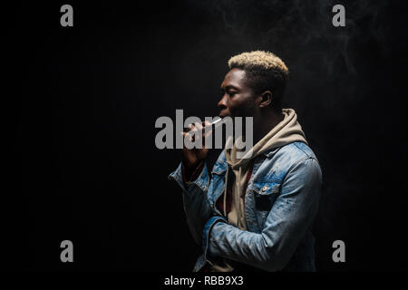 African Man smoking or vaping e-cig or electronic cigarette holding a mod with a lot of clouds isolated on black - Stock Photo