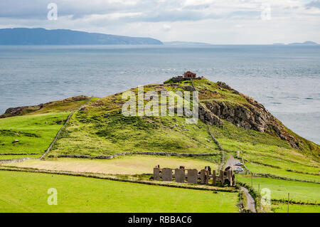 Torr Head headland, rocky cliff and peninsula with ruins of old fort in County Antrim, Northern Ireland, near Ballycastle. Far view of Rathlin Island  - Stock Photo