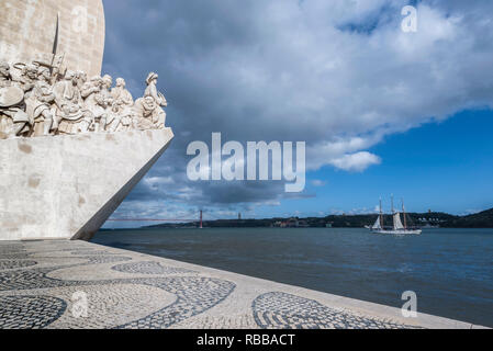 Glimpse of the monument to the discoveries and bridge 25 April on the river Tagus in Lisbon - Stock Photo