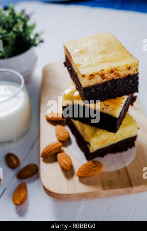 A stack of chocolate cheese cake brownies on wooden background with almonds seed and milk.close up - Stock Photo