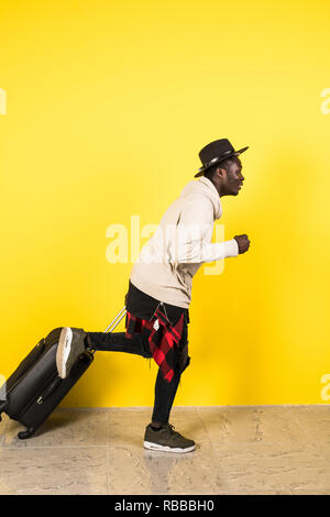 African Tourist man running fast over yellow background - Stock Photo