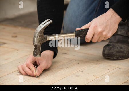 Men Using a hammer and nail on wood , renovation concept - Stock Photo