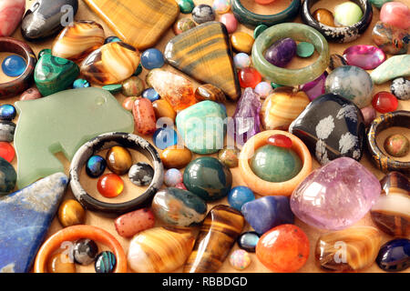 Close up of semi precious tumbled gemstones, cabachons, rings and pendants - Stock Photo