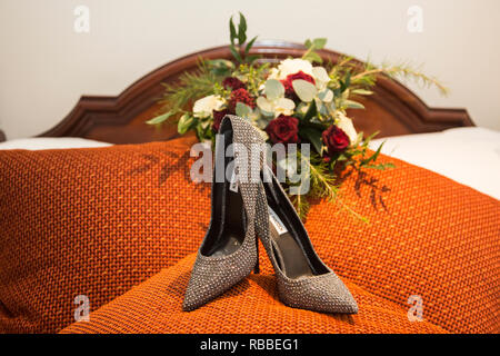 Brides high heeled wedding day shoes, with her bouquet of flowers in the background the shoes are black and silver sparkly high heels. - Stock Photo