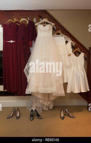 Brides wedding dress and red bridesmaids dresses hanging up waiting to be worn on the wedding day - Stock Photo
