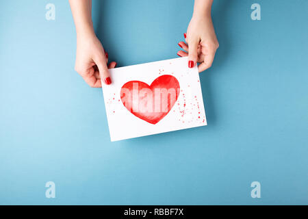 Overhead view on female hands holding card with a painted heart on blue background. Minimal styled composition. Valentine's greeting card. - Stock Photo