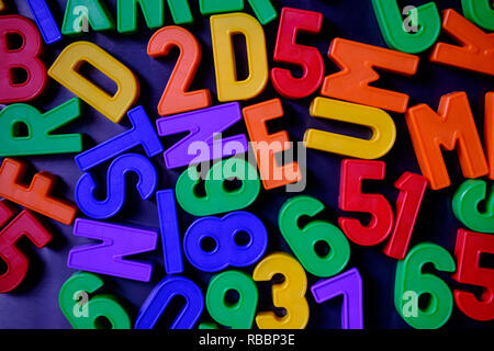 Colorful magnetic numbers and letters grouped on the fridge - Stock Photo