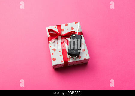 Car key on paper gift box with red ribbon bow and heart on pink table background. Holidays present top view concept. - Stock Photo