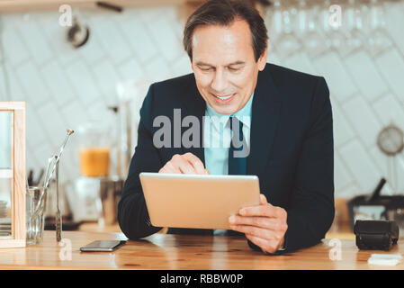 Making research. Handsome man in black suite holding tablet searching information in internet - Stock Photo