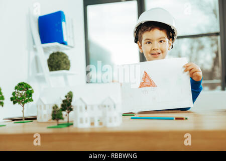 Drawing a house. Lovely boy wearing a helmet and smiling while showing his cute picture of a house - Stock Photo