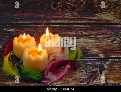 Three burning candles in the shape of egg halves covered with colorful feathers on an old wooden background in vintage styles.Interesrting easter comp