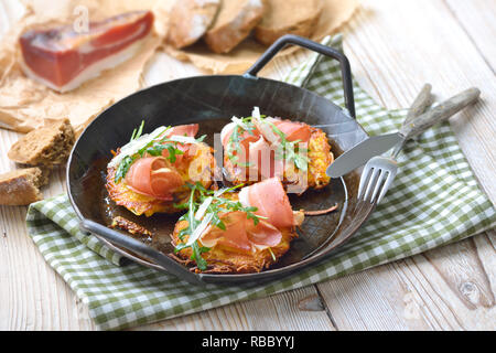 Potato rosti with South Tyrolean bacon, parmesan cheese and rocket salad served in an iron frying pan - Stock Photo