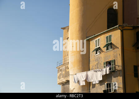 Laundry drying at the sun from house near Basilica Santa Maria Assunta in Camogli. Genoa, Ligury Italy - Stock Photo