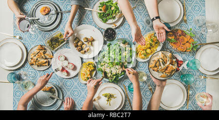 Flat-lay of human hands holding mediterranean starters and drinks - Stock Photo