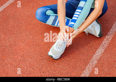 Leg Injury. Woman runner suffering from pain in leg after workout is touching ankle outdoors at stadium - Stock Photo