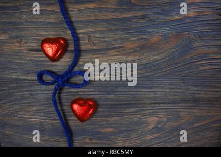 Holiday decor layout on wooden background with heart-shaped red candies, decorated with blue tread with bow. Viewed from above with copy space - Stock Photo