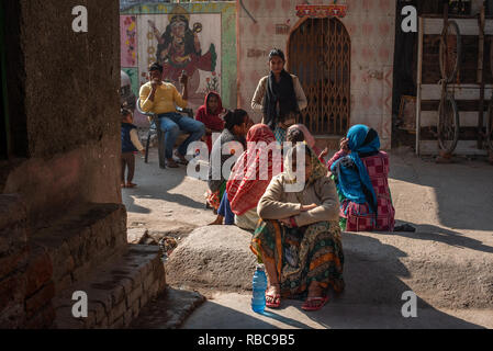 Life on the streets on a wintery sunny afternoon in JJ Colony Madanpur Khadar, New Delhi - women group together sitting in front of a temple. - Stock Photo