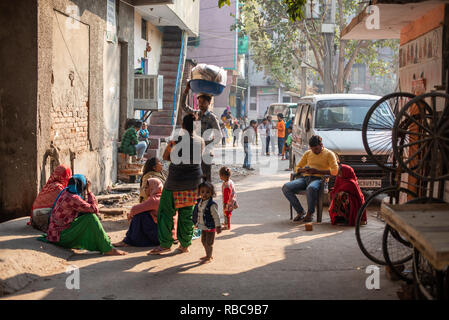 Life on the streets on a wintery sunny afternoon in JJ Colony Madanpur Khadar, New Delhi - people group together approached by a vendor. - Stock Photo
