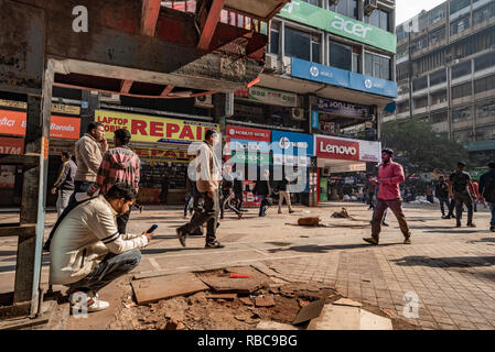 A man checks mobile phone underneath a staircase while passersby walk around in the busy Nehru Place centre of digital technology, New Delhi, India - Stock Photo