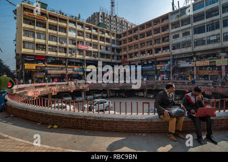 View of a courtyard in Nehru Place, New Delhi, India which is the hub of digital technology: scene shows two people in foreground sitting in the sun. - Stock Photo