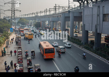 View of the travel interchange outside Sarita Vihar Metro station in New Delhi with rickshaws waiting for customers, buses and traffic moving. - Stock Photo