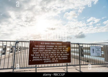 Old Bahia Honda Bridge Trail in state park during day in Florida Keys, with hiking path, closeup of sign on fence, nobody, sun behind clouds in sky - Stock Photo
