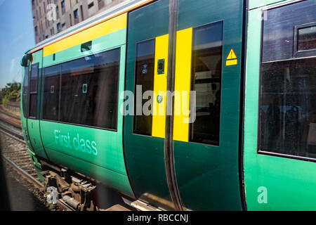 London, UK - June 28, 2018: Southern Rail green metro subway train in London Victoria Station railroad rails motion moving with green first class sign - Stock Photo