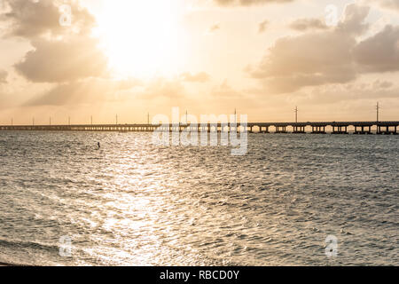 Seven Mile Bridge landscape of Florida Keys reflection of sun on water atlantic ocean and Overseas Highway road with horizon clouds sunset rays - Stock Photo