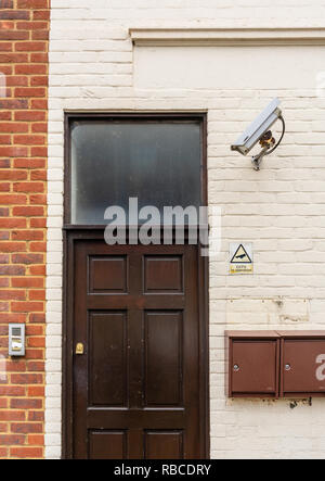 CCTV surveillance camera mounted on a wall outside an entrance door to residential flats in Southampton, England, UK - Stock Photo