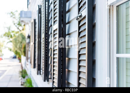 Black decorative row of window shutters closeup architecture open exterior of houses buildings or homes in Charleston, South Carolina southern city - Stock Photo