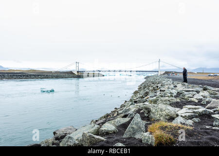 Jokulsarlon, Iceland - June 15, 2018: Glacial lagoon lake river with many icebergs floating by route one 1 bridge over water with people standing watc