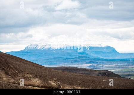 Landscape view of Iceland mountain in Krafla near lake Myvatn during cloudy day and closeup of snowcapped volcano - Stock Photo