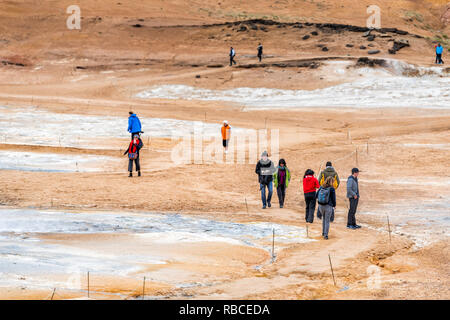 Hverir, Iceland - June 16, 2018: Hot fumaroles with people tourists looking at springs on trail path high angle view with geyser in geothermal spot ar - Stock Photo
