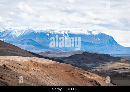 Landscape closeup view of Iceland mountain in Krafla near lake Myvatn during cloudy day and snow on volcano - Stock Photo