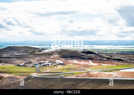 Reykjahlid, Iceland - June 16, 2018: Landscape high angle view of lake Myvatn and fumaroles steam vents during cloudy day and car on road highway - Stock Photo